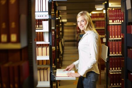 industriousness: Blonde woman standing with book in library