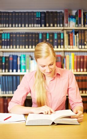 industriousness: Female student reading a book and making notes