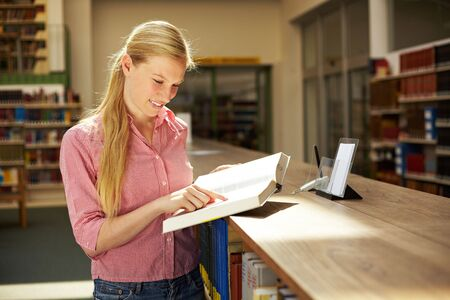 industriousness: Female student standing in library and reading a book Stock Photo