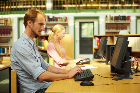Students sitting in library and using computers photo