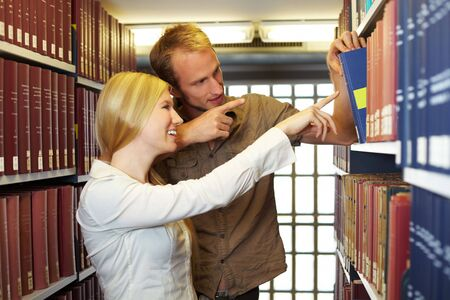 industriousness: Two students taking books from a shelf Stock Photo