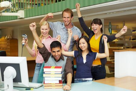 Library staff at university cheering at counter Stock Photo - 5917002