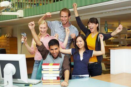 Library staff at university cheering at counter Stock Photo - 5917002