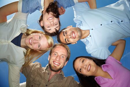 Five happy friends embracing under blue sky Stock Photo - 5916999