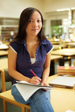 industriousness: Asian student studying in library at university