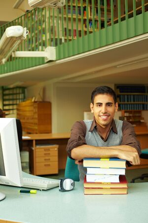 Friendly librarian sitting at desk with books photo