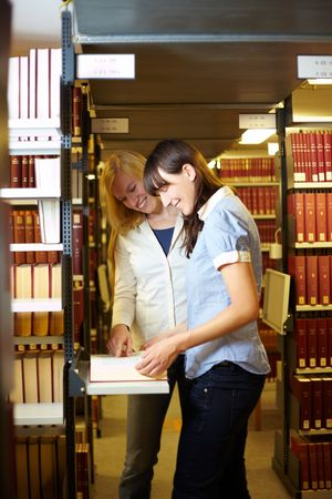 industriousness: Two students reading a book in library Stock Photo
