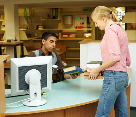 librarian: Employee scanning books in library at counter Stock Photo