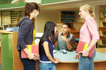 Students chatting while checking out books in library photo