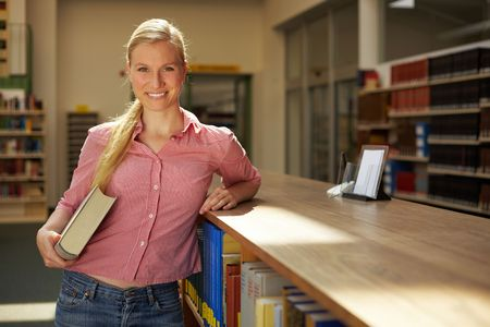 industriousness: Happy student standing in reading room of library