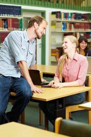 Student talking with a female student in library Stock Photo - 5931999