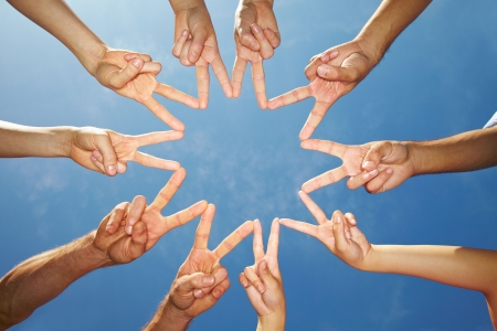 games hand: Many hands connecting to star shape under sky Stock Photo