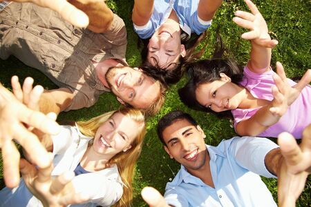 Happy students on lawn stretching their arms Stock Photo