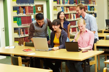 netbook: Group of students learning in library at university Stock Photo