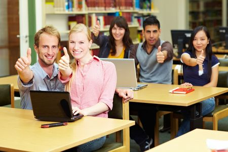 Five students holding their thumbs up in library Stock Photo - 5932006