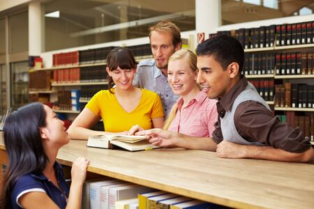 Group of students looking in book at library photo