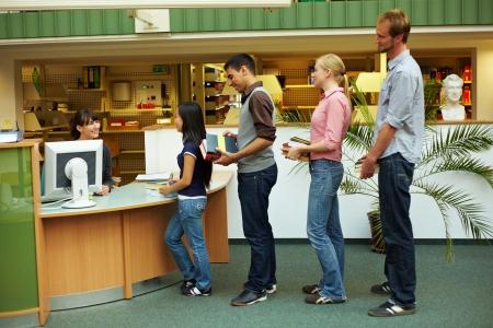 Estudiantes esperando en línea en la biblioteca de la Universidad  Foto de archivo - 5931979