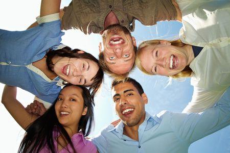 Five happy friends embracing under blue sky