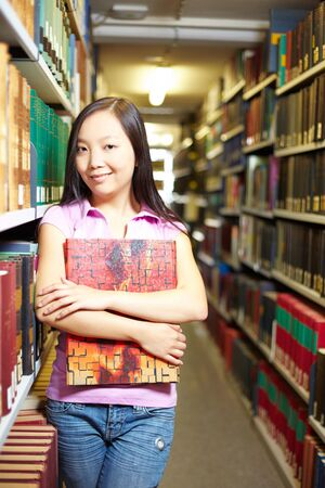 industriousness: Asian student standing in library at university