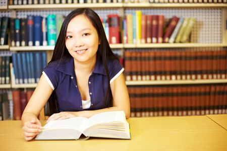 industriousness: Asian student reading book in a library Stock Photo