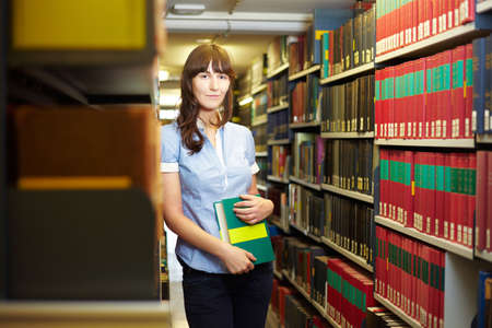industriousness: Student with book leaning on shelf in library