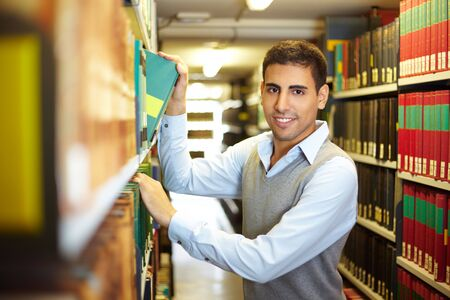 Student looking for a book in library archive photo