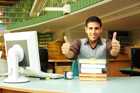 Happy librarian at desk holding his thumbs up photo