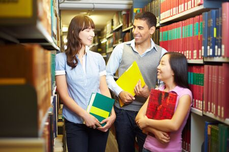 industriousness: Students with books talking in library archive
