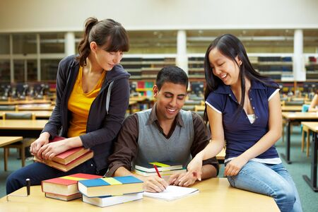 Three happy students learning in university library Stock Photo - 5931996