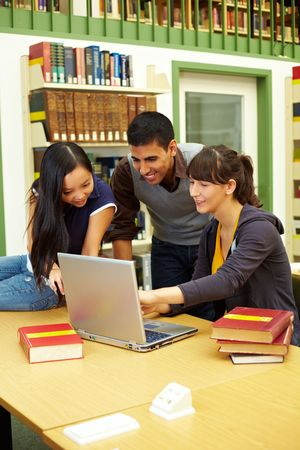 Three happy students learning in university library photo