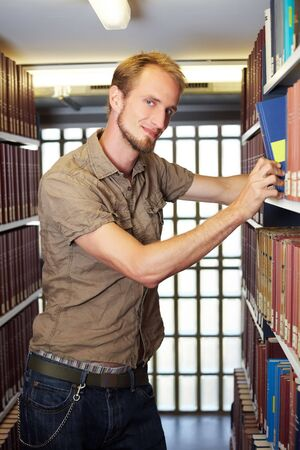 industriousness: Student looking for book in library archive Stock Photo