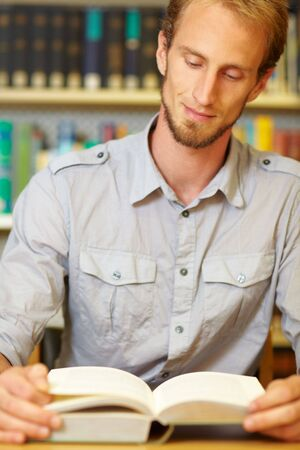 industriousness: Student reading a book in library archive Stock Photo