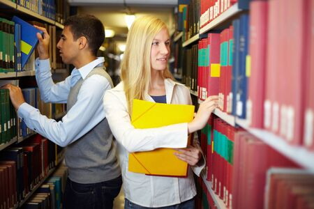 industriousness: Two students doing research in a library