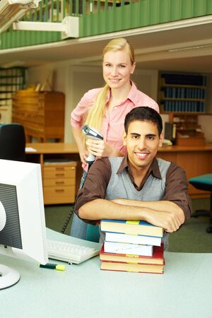 Two employees in a library at checkout counter photo