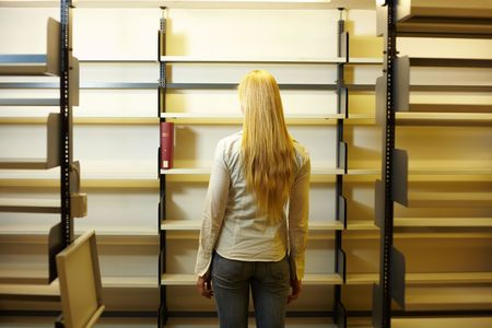 Student looking at empty book shelves in library