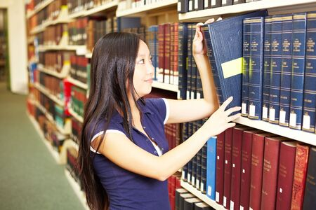 Asian student taking book from a shelf photo