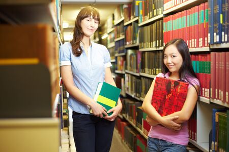 industriousness: Two students with books in library archive