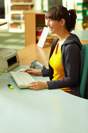 Library staff sitting at checkout counter in library photo