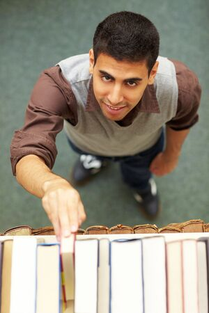 industriousness: Student taking a book from shelf in library