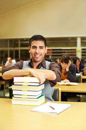 Student with books sitting in reading room at library photo