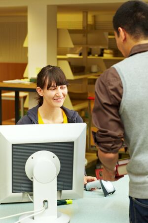 Student renting books at university library checkout photo