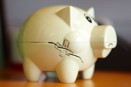 Damaged piggy bank with crack and plaster painted on Stock Photo - 6053483