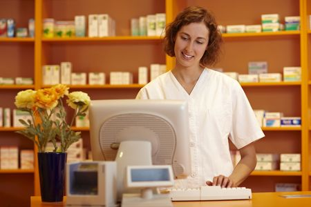 Pharmacist typing on computer behind pharmacy counter photo