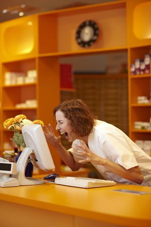 Female pharmacist screaming at computer on counter photo