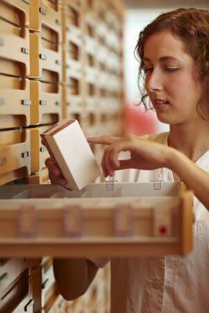 adverso: Farmac�utico leer la informaci�n de uso en medicina de embalaje