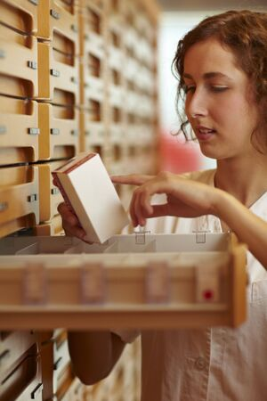 adverse: Pharmacist reading usage information on medicine packaging