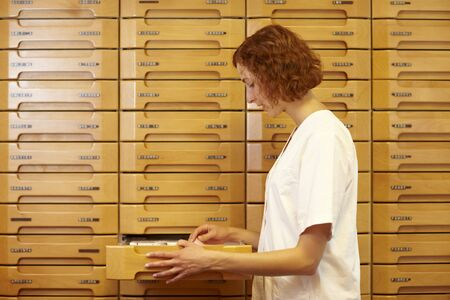 Pharmacist reaching for drawer at medicine cabinet photo