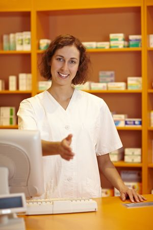 Pharmacist behind counter reaching out with her hand photo