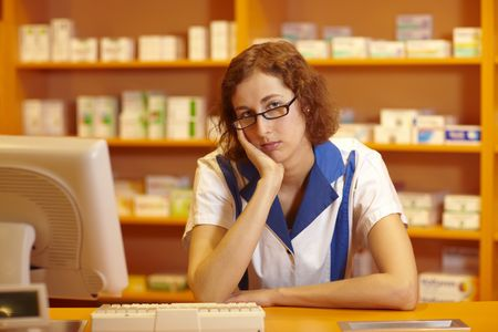 Female pharmacist behind counter waiting for customers photo