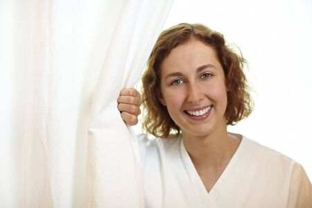 Happy young nurse pulling white curtain aside Stock Photo - 6053493